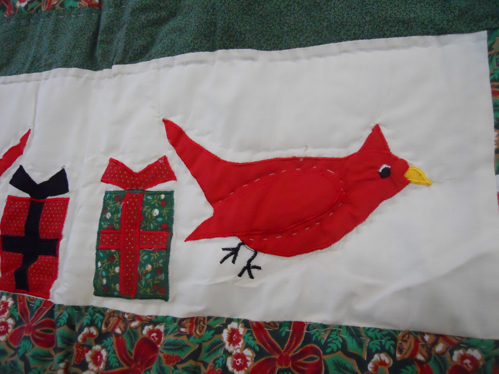 Simple applique red cardinal birds add country charm to Happy Holidays Cardinals Quilt Throw.