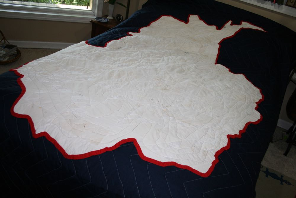 The finished Australian continent art quilt on a double bed to give you the scale of the quilt.