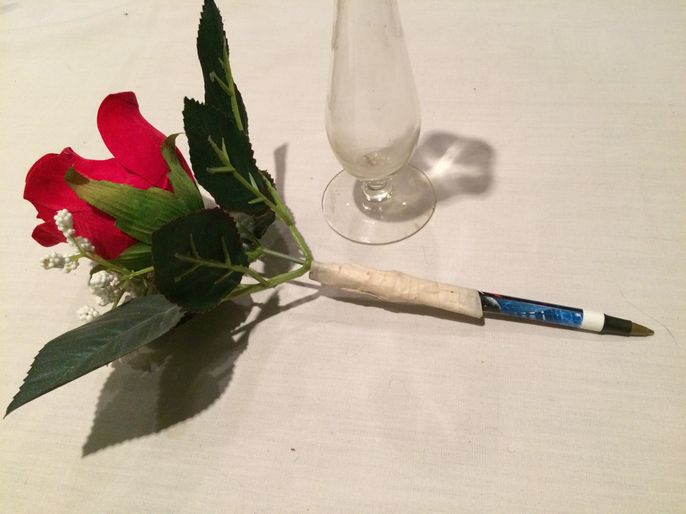 This gift was quickly made by wrapping tape around a silk flower and writing pen.
