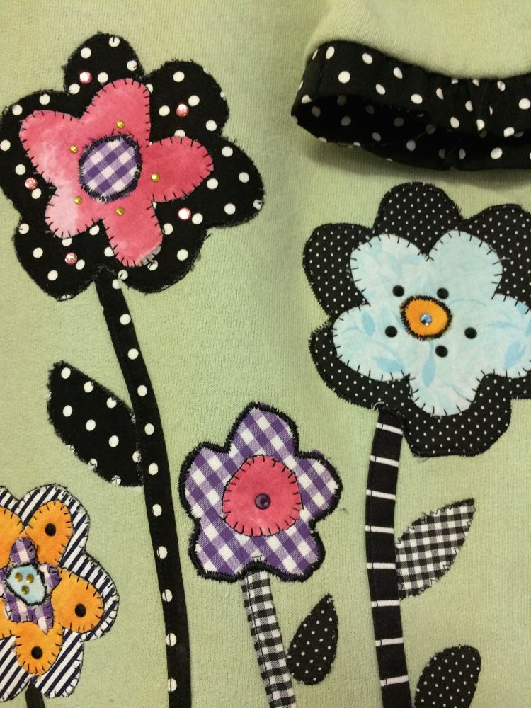 Below the butterfly, a very sweet blooming garden of applique fabric flowers.