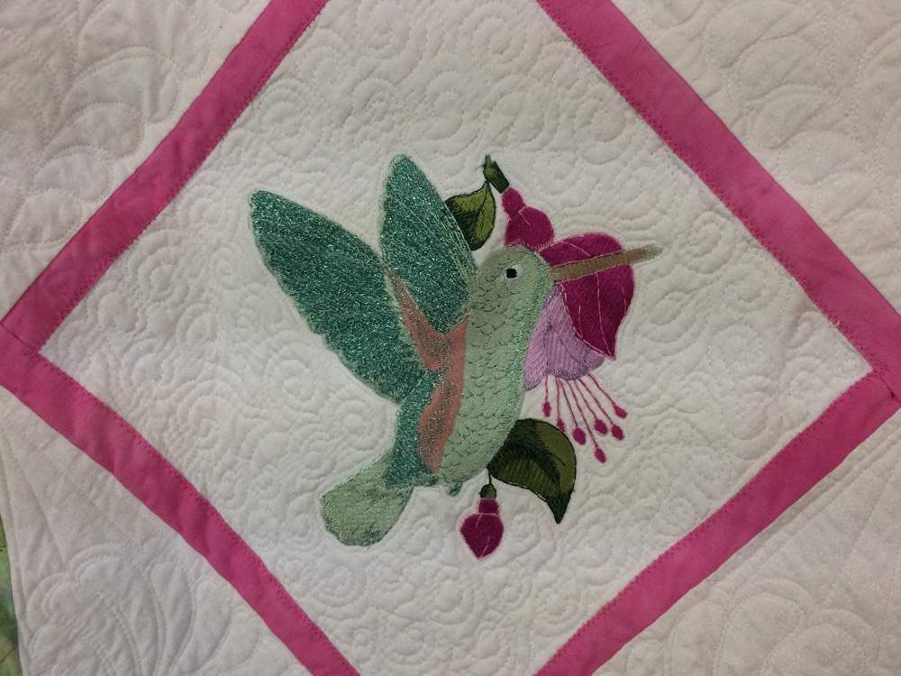Beautiful hummingbird against a fuchsia on a detailed quilted white background.