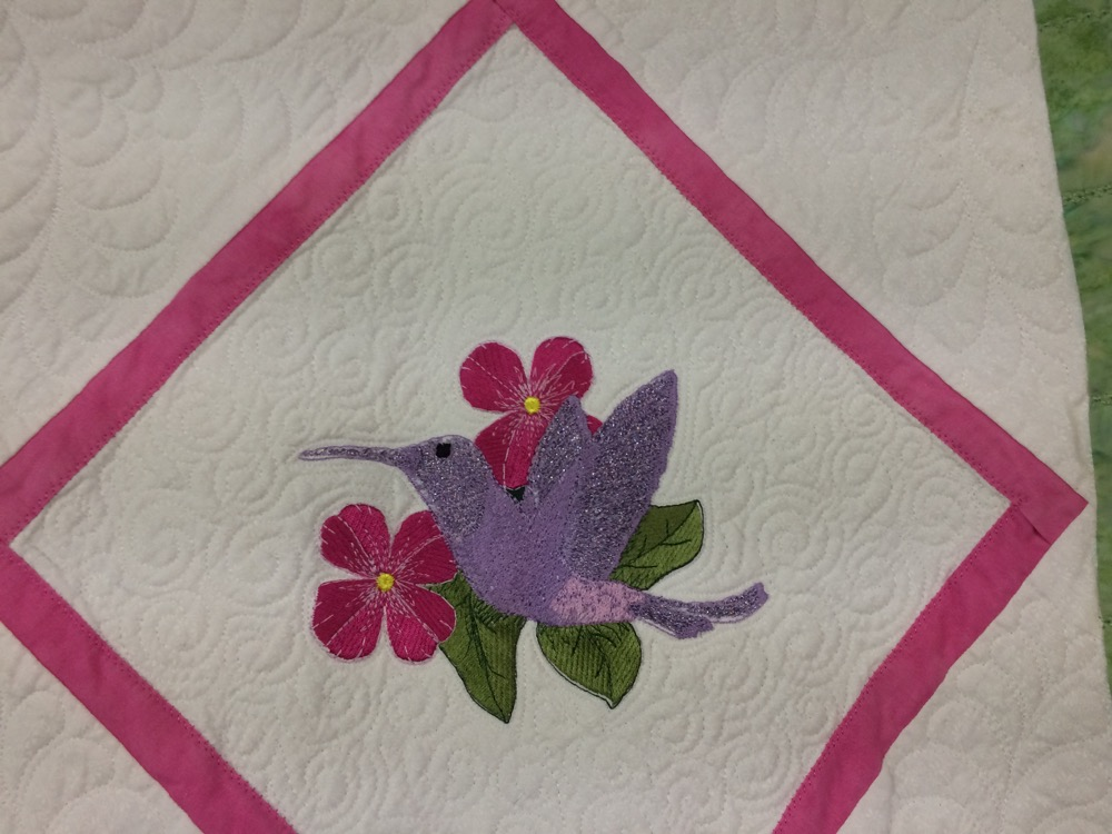 Purple hummingbird on a pink flower against a detailed quilted white background.