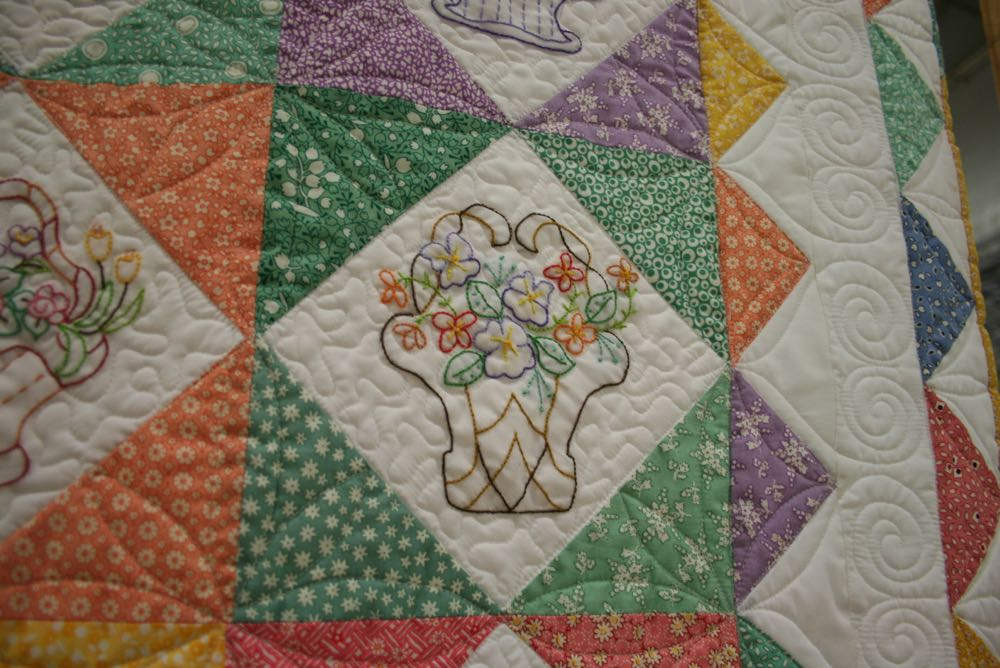 Another embroidered basket quilt block featuring green fabrics in the quilt block.