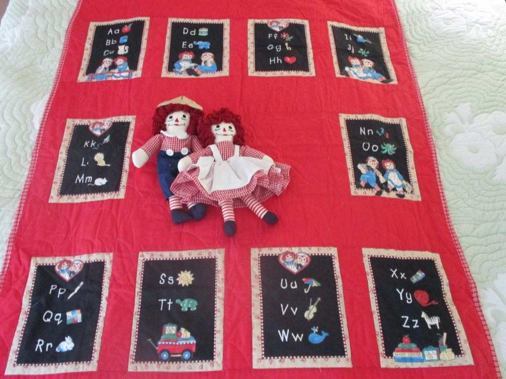 The classic Raggedy Ann and Andy colors are incorporated into this alphabet baby quilt.