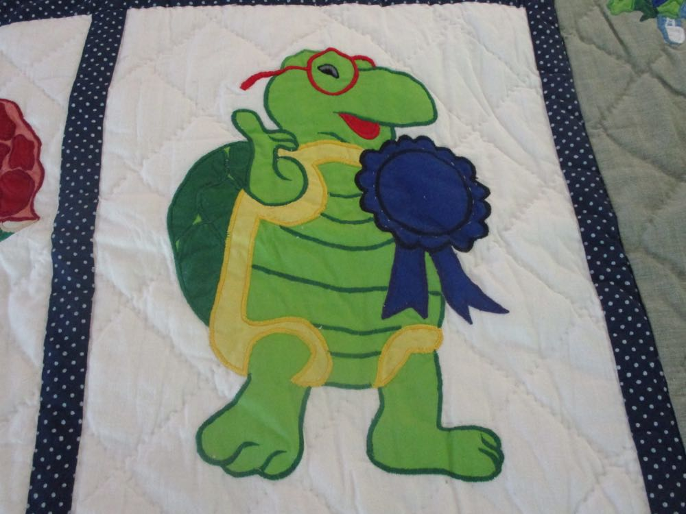 """Winning"" turtle with a first place ribbon in one of the blocks of this handmade quilt throw."