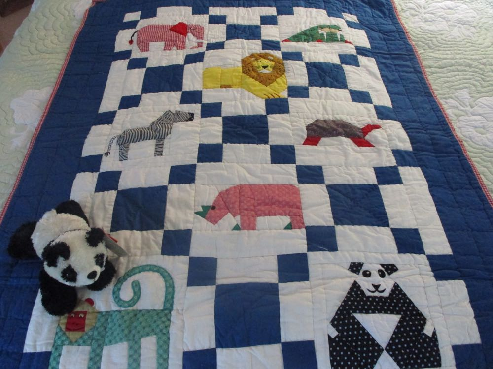 Applique and embroidery combine in this charming zoo baby crib quilt.