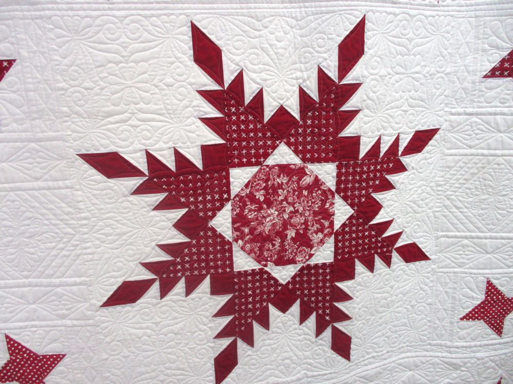 Center block of this red and white handmade quilt raffled by Piece and Plenty Quilt Guild.