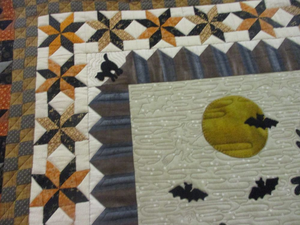 The detailed machine quilting gives Ichabod Hollow Handmade Quilt Wall Hanging nice texture.
