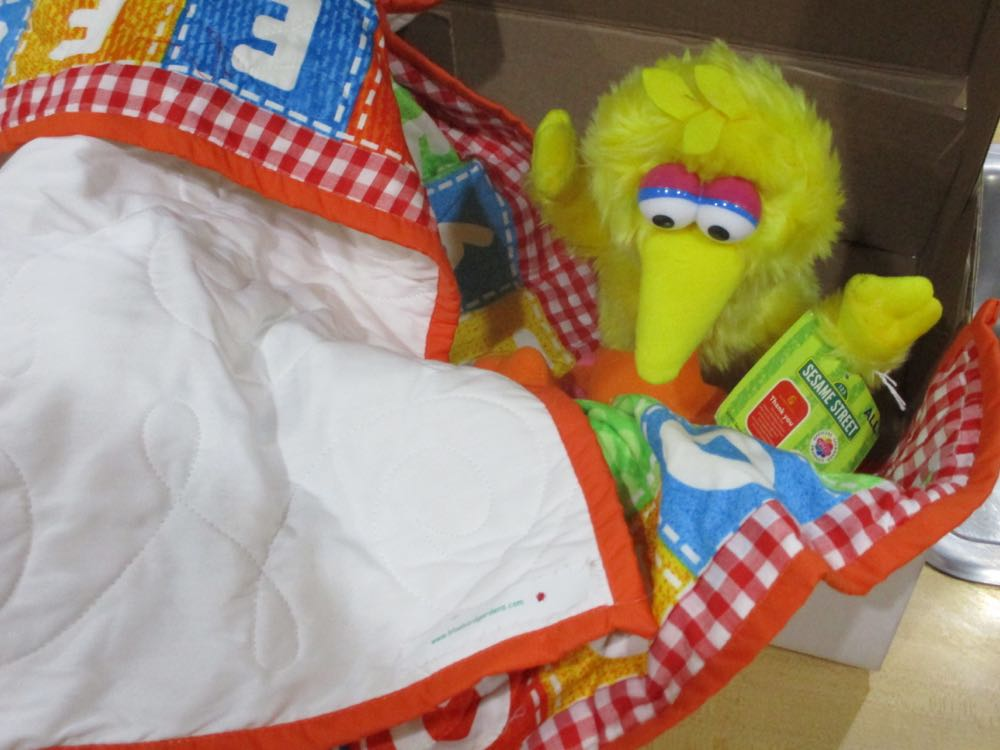 Big Bird inspects my sewing after I finished adding a label to a custom baby quilt.