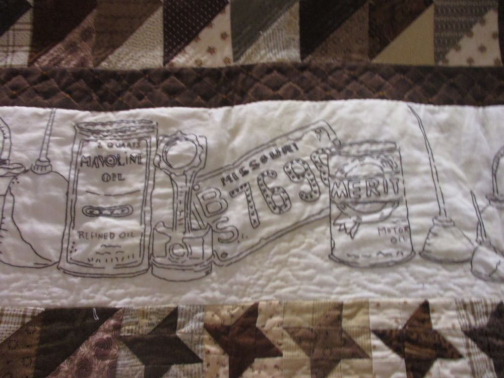 Close up of the old oil cans in the top banner of the winning handmade quilt.