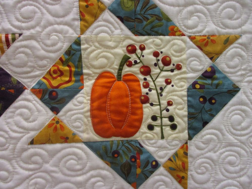 Cute orange pumpkin block sits in the middle of the detailed quilting in the white space.