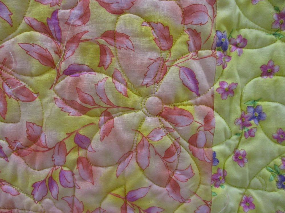 Close up of the machine floral quilting in this winning beginning patchwork quilt.