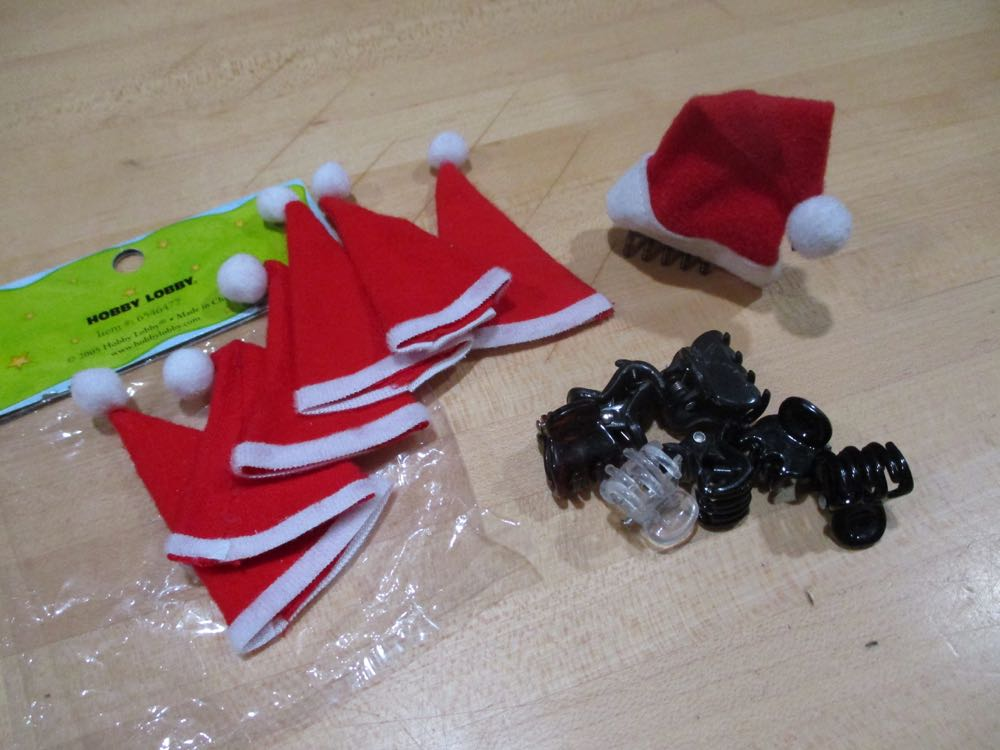 Tiny Santa hats, hair clips and a hot glue gun or needle and thread is all you need.