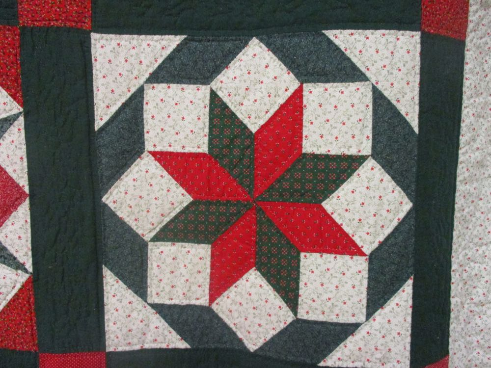 One of the star-shaped quilt blocks in this Christmas Sampler handmade quilt.