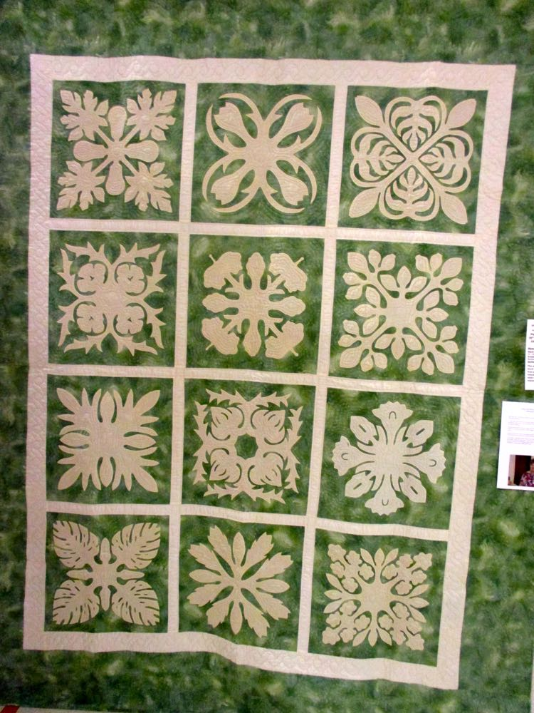 This version of a Hawaiian Floral quilt features different flowers in each of the handmade quilt blocks.