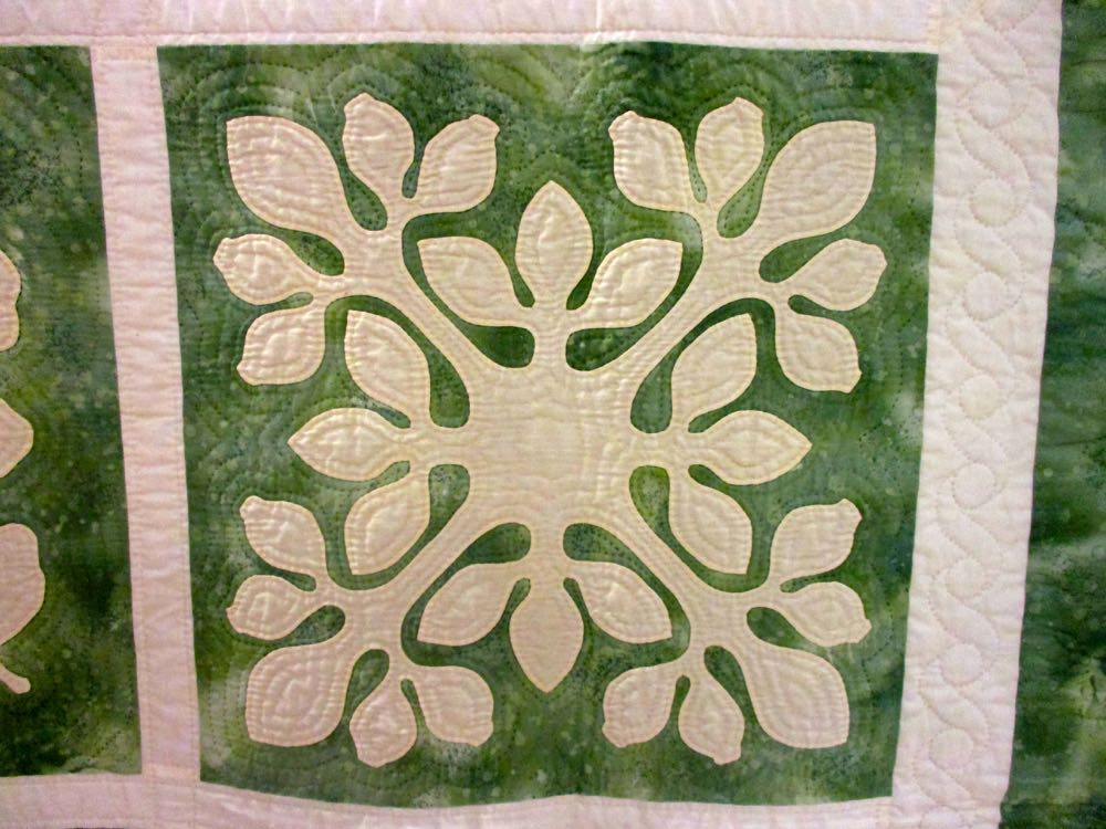 Look at how the hand quilting adds texture to this floral block in the Hawaiian Floral handmade quilt.