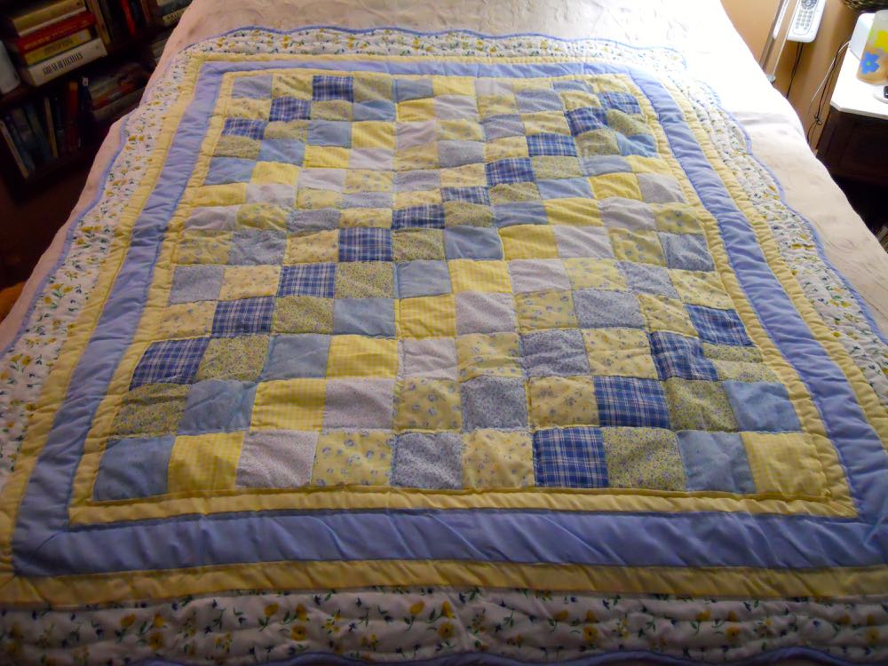 Blue Yellow Ninepatch Lap Quilt Wall Hanging on a bed to show all of the included fabric colors.