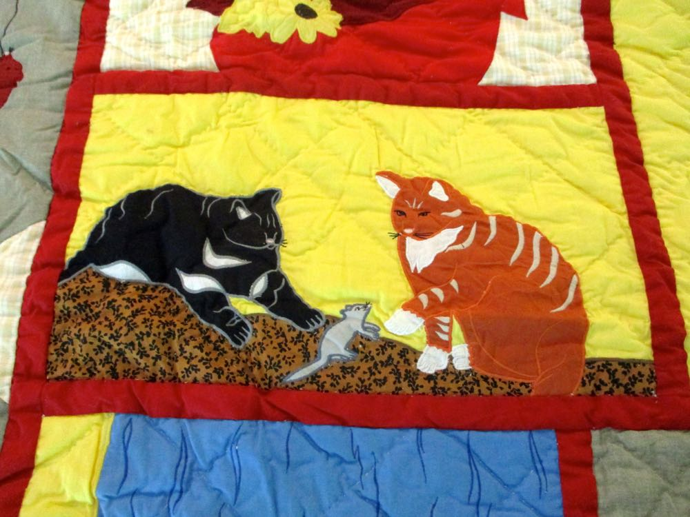 Two cats play with a grey mouse in Cat Mischief Lap Quilt Wall Hanging.
