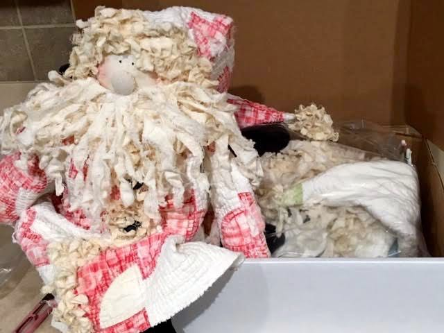 One of two Santa dolls from cutter quilts climbing into the shipping box. (Photo by Charlotte Ekker Wiggins)