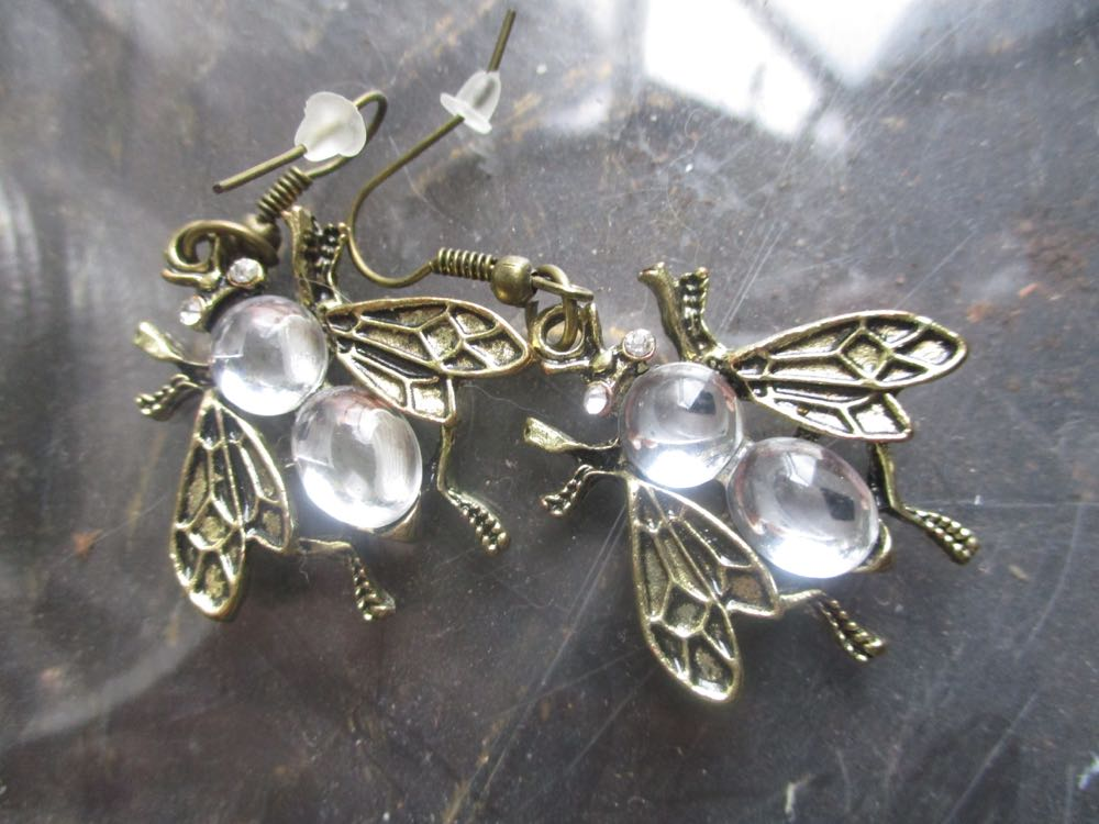 These bee-themed earrings include clear bodies, probably a clear plastic or polymer.