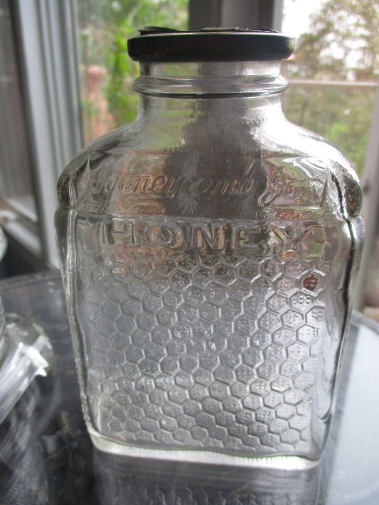 This is a vintage glass jar for honey with the old original lid, love the comb pattern on the side.