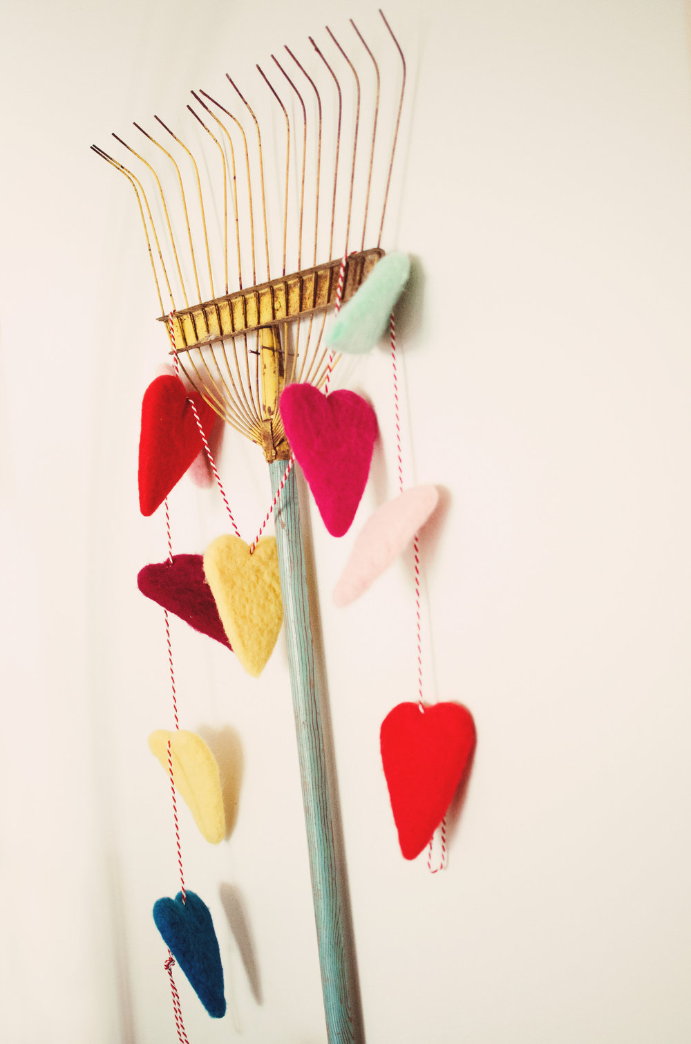 Vintage rake used as wall decor with heart garland. H.Prall & Co. | hprallandco.com