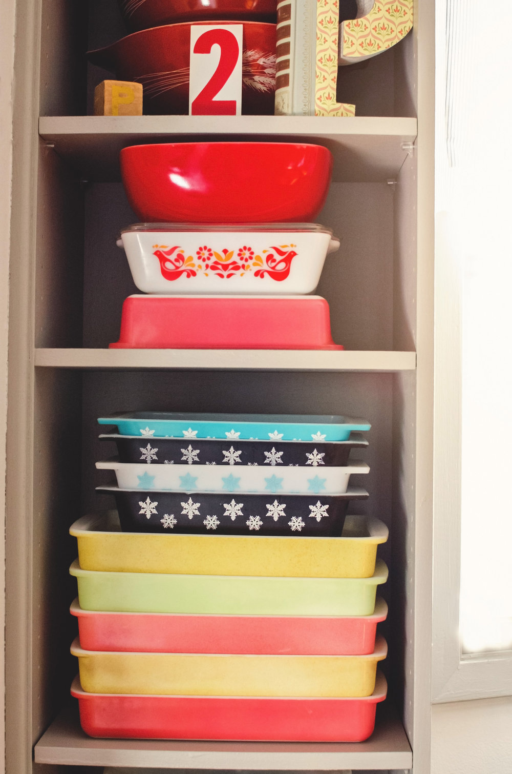 Colorful vintage pyrex stacked on shelves. H.Prall & Co. | hprallandco.com