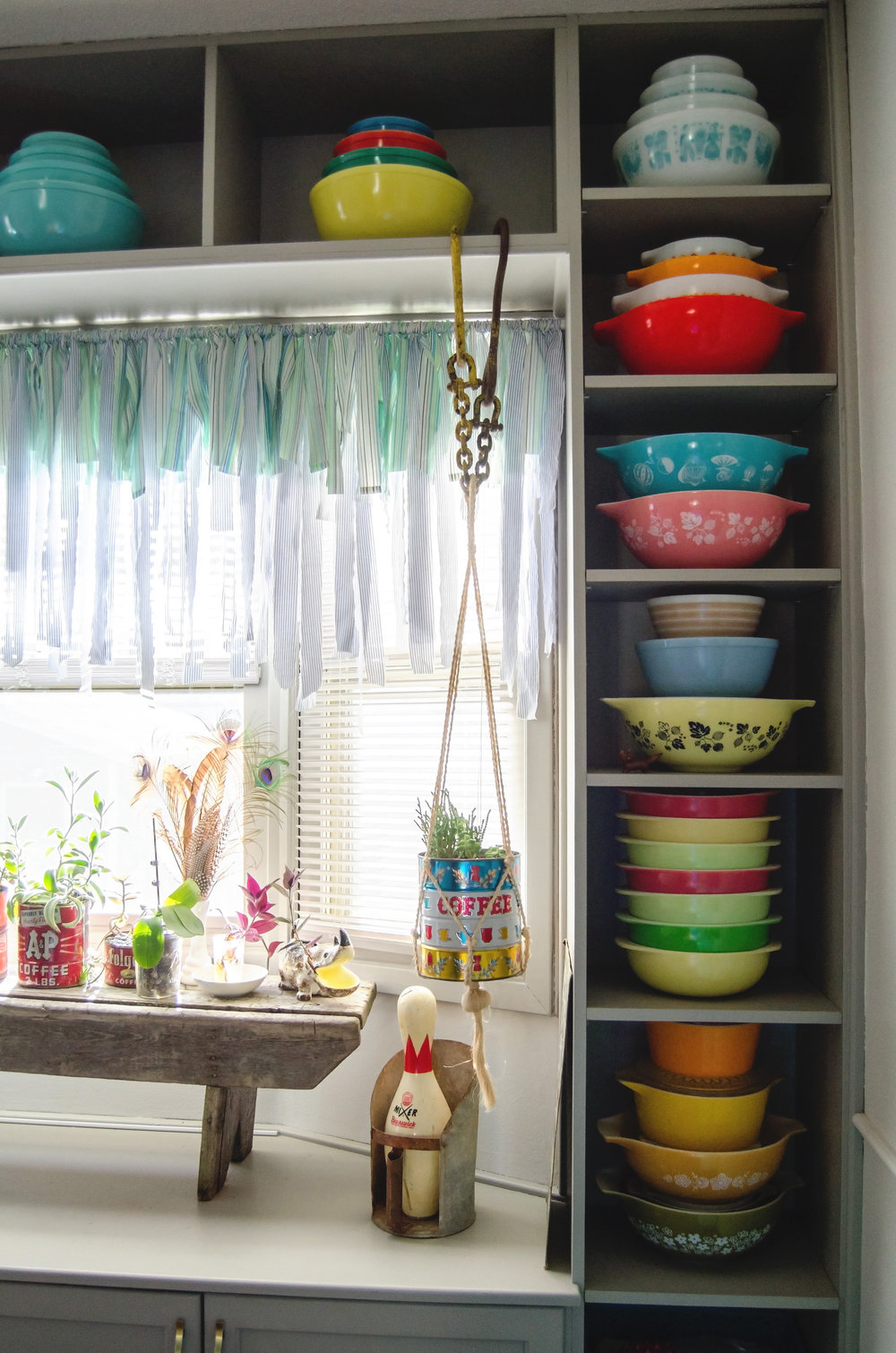 Side shelving full of colorful vintage Pyrex pieces. H.Prall & Co. | hprallandco.com