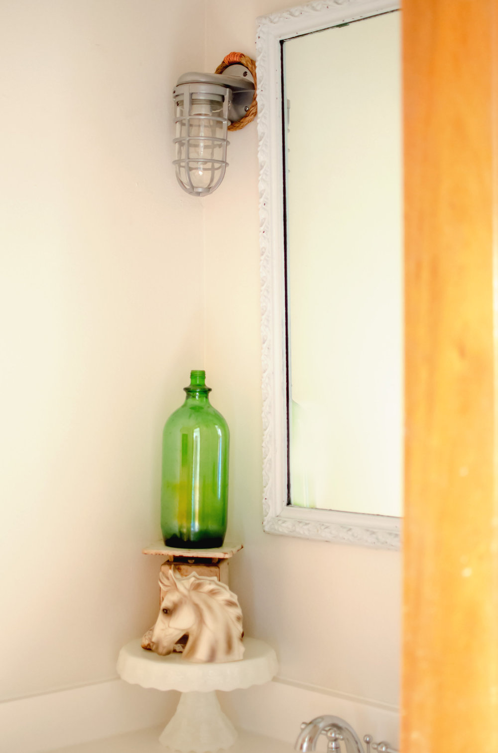 Vintage green glass bottle with a horse figurine as unique and unexpected decor. | hprallandco.com