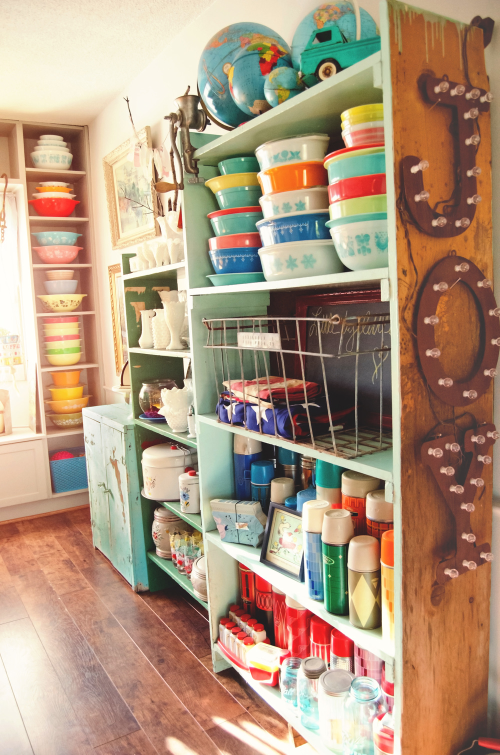 Kitchen shelves filled with bright, colorful vintage dishes and, and milk glass pieces. || RustopiaConsulting.com