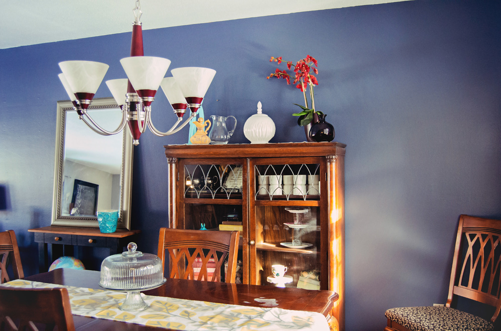 Blue dining room wall with pops of red in the light fixture and accessories. | hprallandco.com