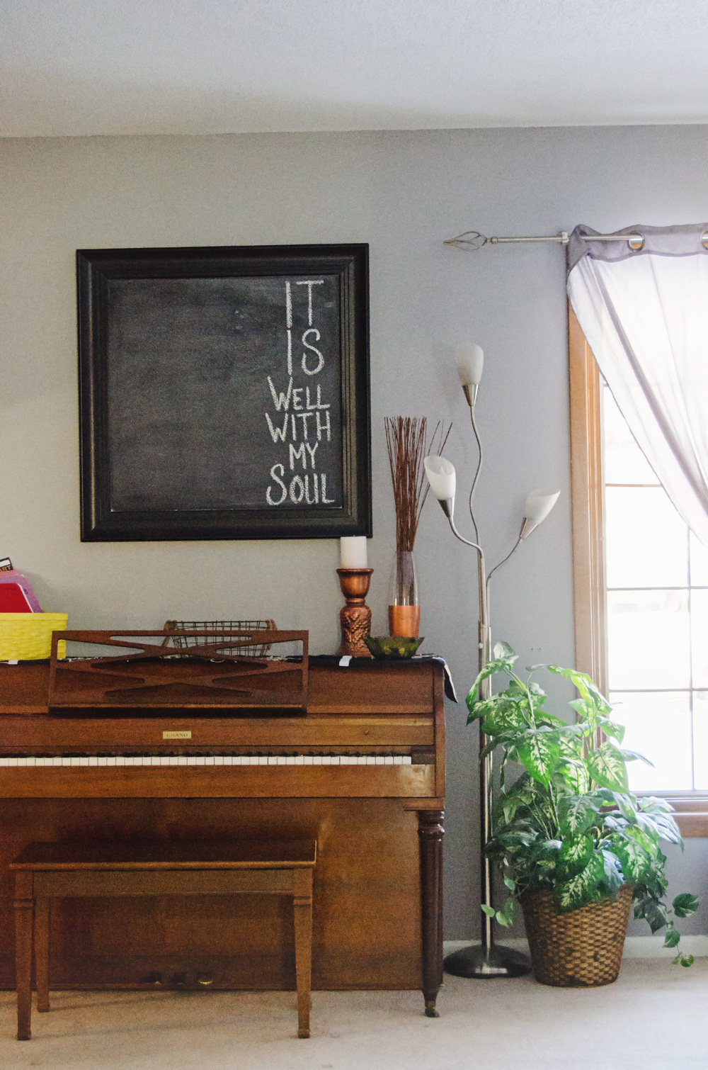 Framed chalkboard as wall decor hanging over a piano. | hprallandco.com