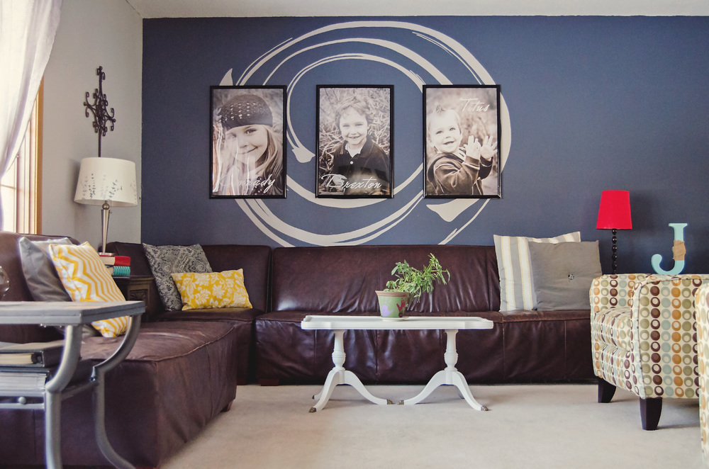 Living room with a blue accent wall and oversized family photos. | hprallandco.com