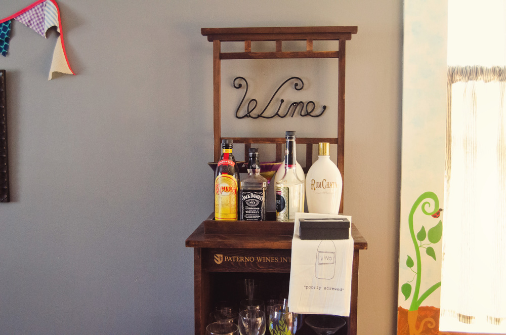 Bar area with a wine sign hanging above. | hprallandco.com