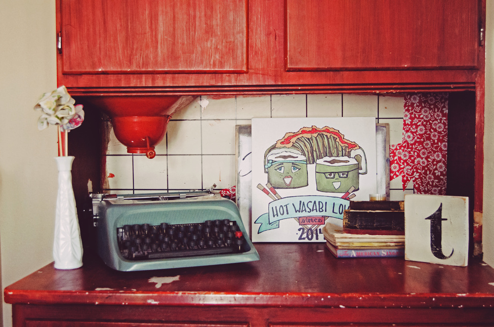 Red cabinets with a blue vintage typewriter. H.Prall & Co. | hprallandco.com