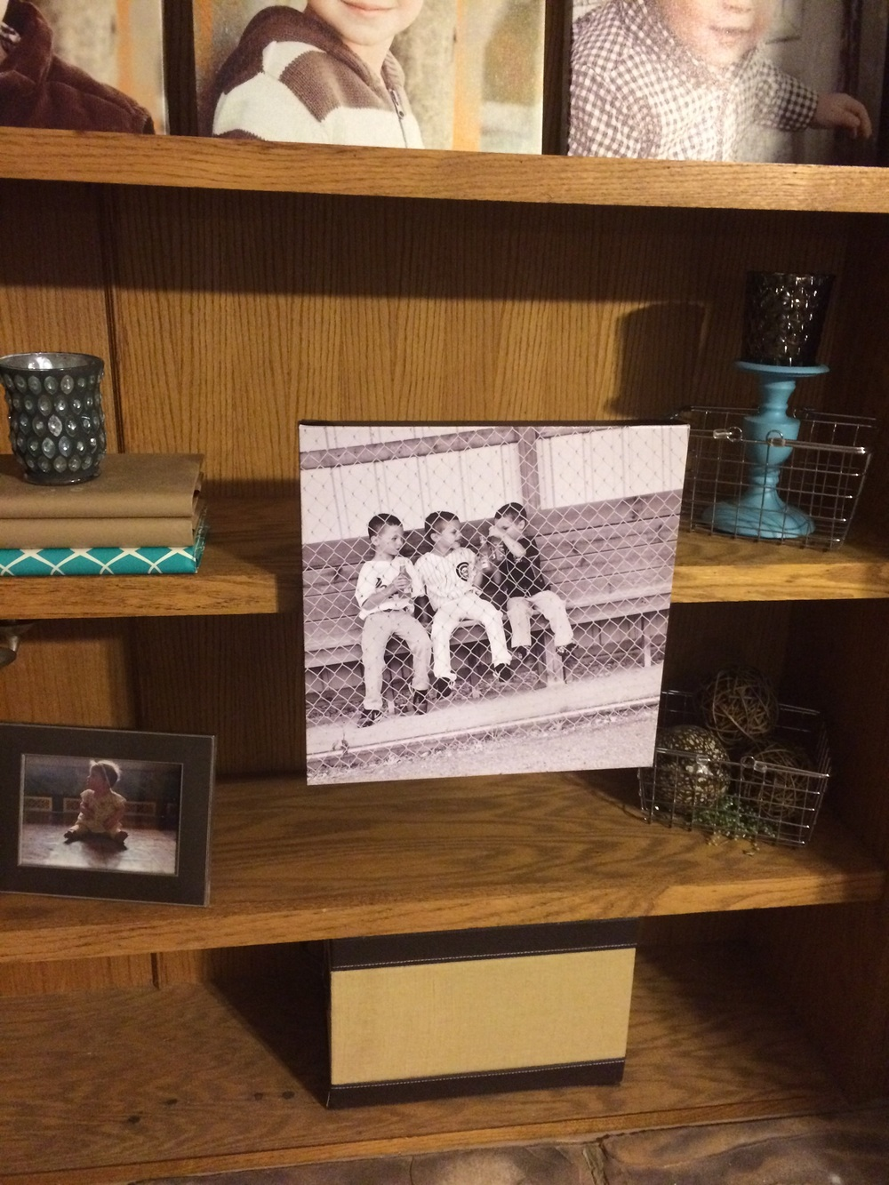 Photographs attached to the front of shelves using Command Strips. || RustopiaConsulting.com