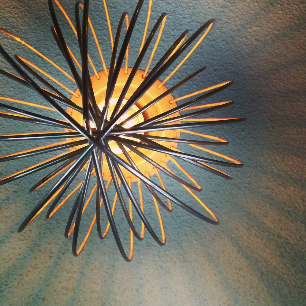 Close up of a re-purposed mixer whip as a light fixture. ||RustopiaConsulting.com