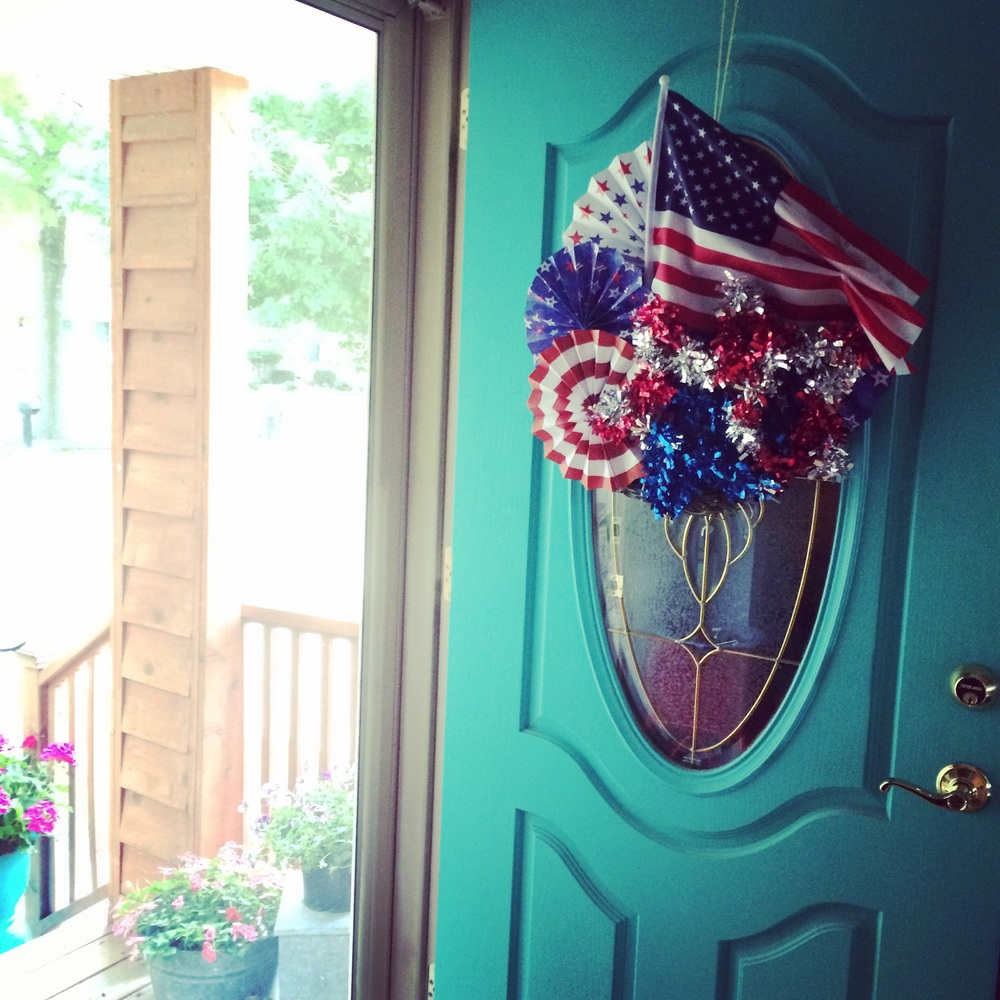 Americana decorations hanging on a turquoise front door. || RustopiaConsulting.com
