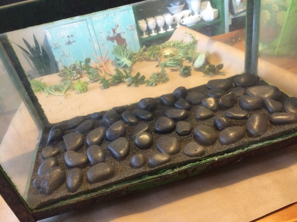 A layer of medium sized stones at the bottom of an aquarium for a DIY terrarium project. || RustopiaConsulting.com