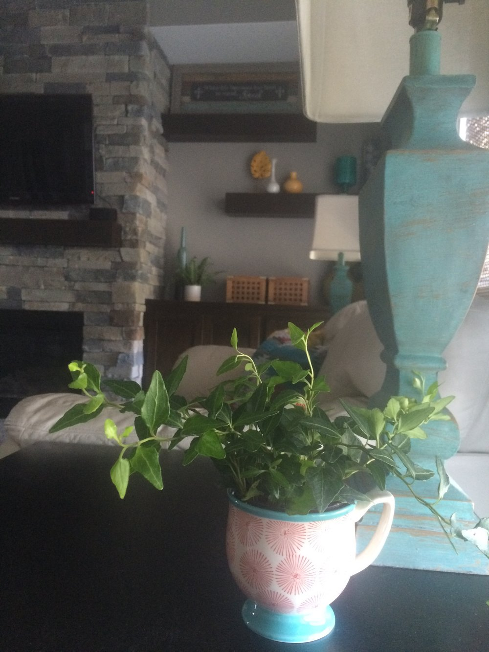 Coffee cup with greenery and a table lamp on a living room end table. || RustopiaConsulting.com