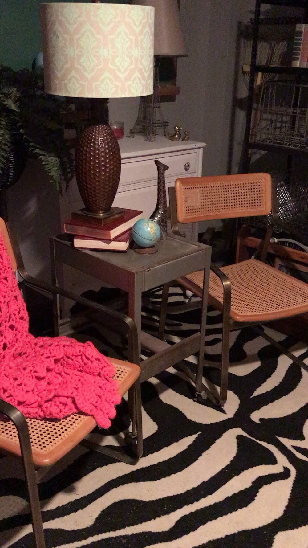 End table with a large table lamp between two vintage chairs with a pink crochet blanket on a zebra print rug. RustopiaConsulting.com