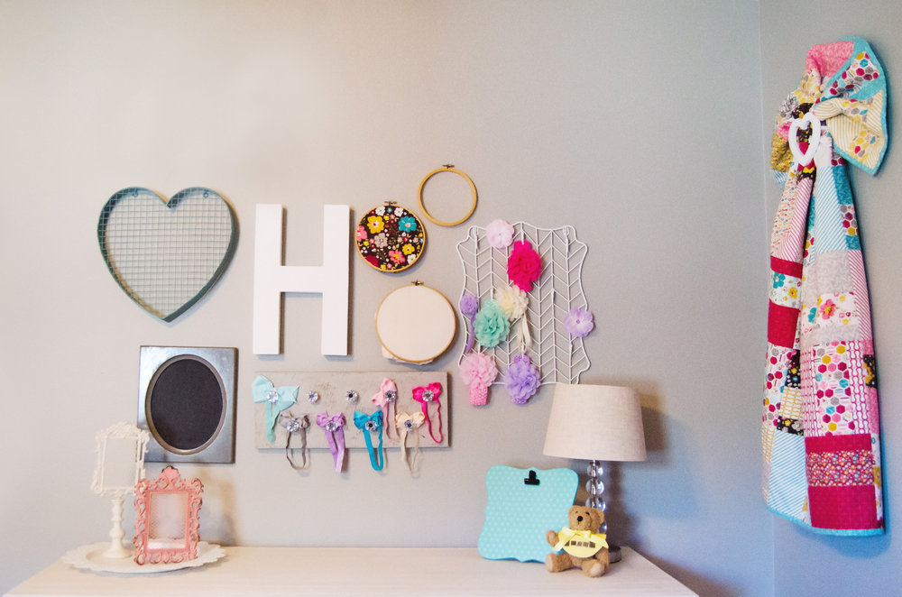 Baby girl bow holders as wall decor in a gallery wall. | hprallandco.com