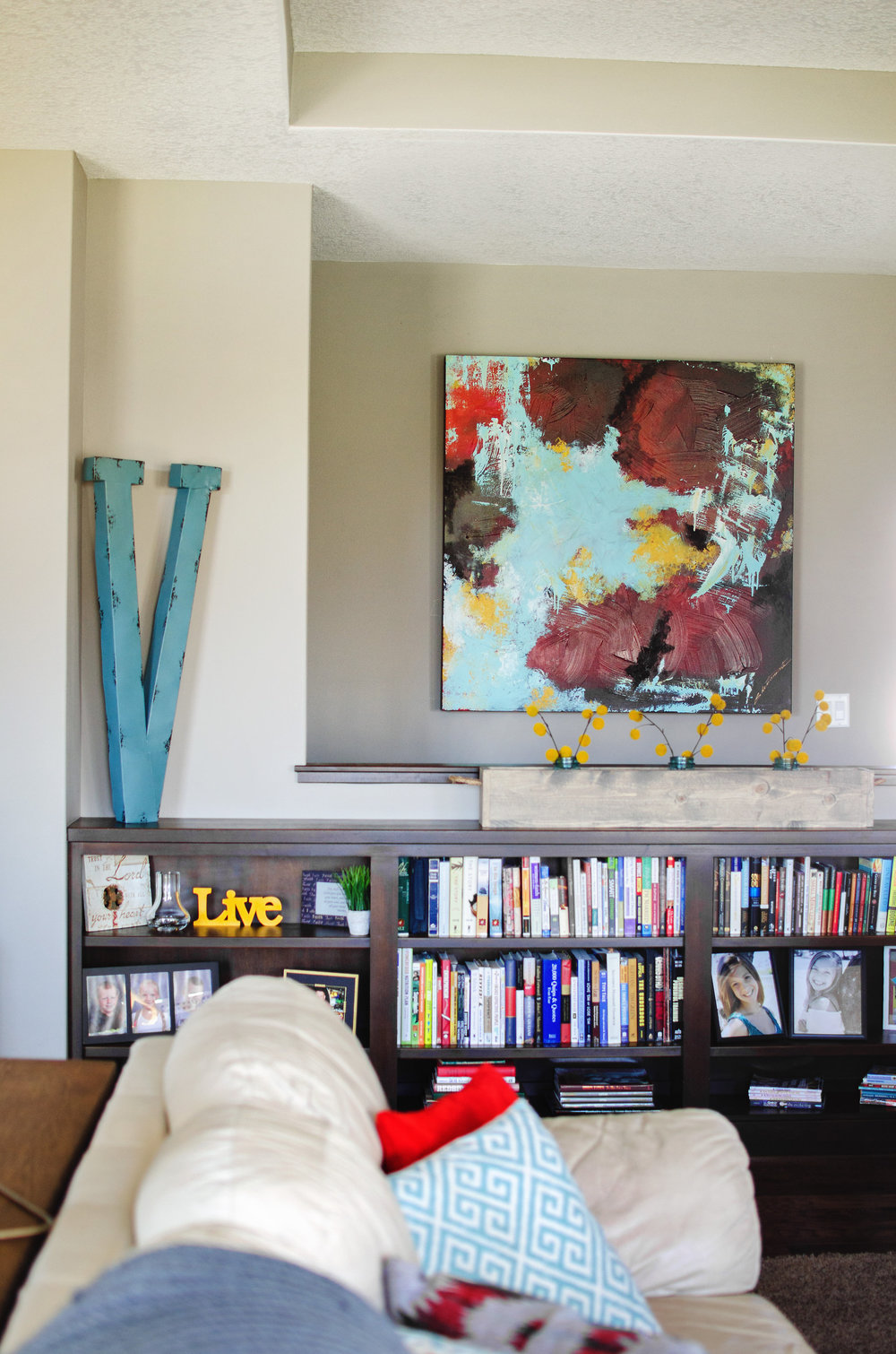 Abstract painting and over-sized monogram over a bookshelf. | hprallandco.com