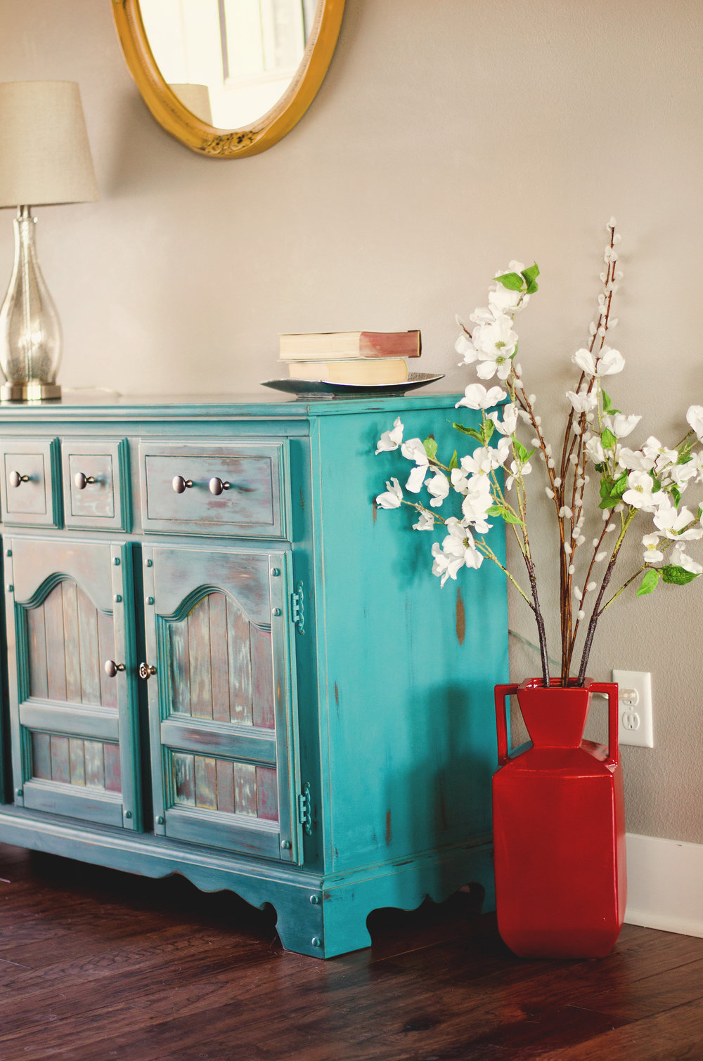 Turquoise cabinet and large red vase with flowers. H.Prall & Co. | hprallandco.com
