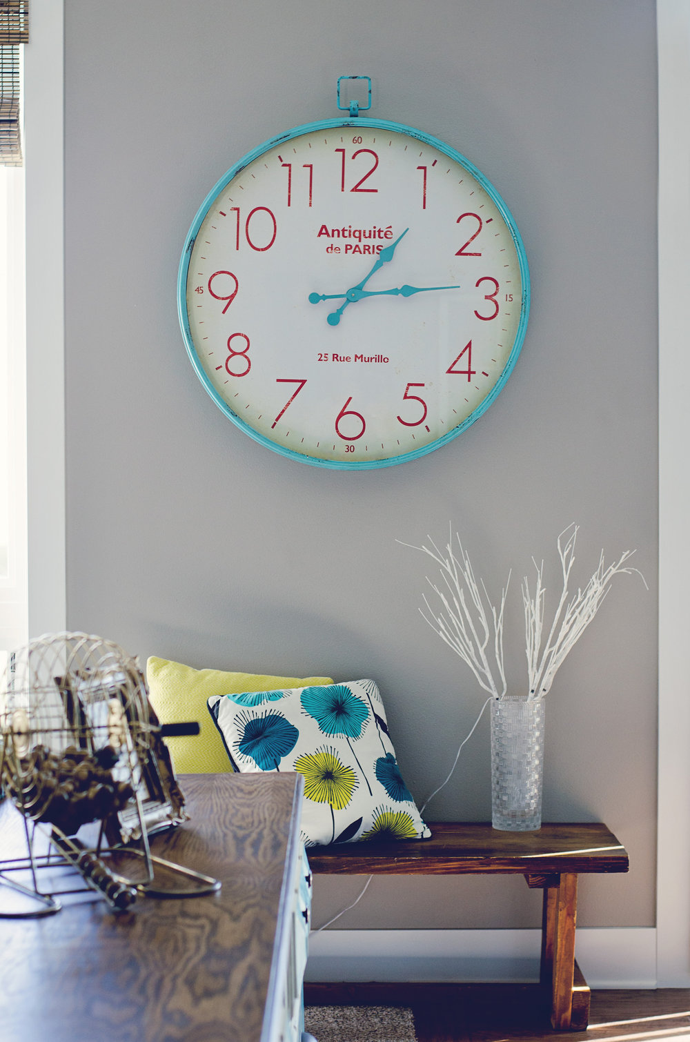 Turquoise and red wall clock over a bench. | hprallandco.com