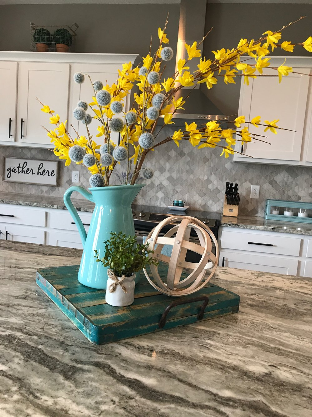 Kitchen vignette using a turquoise wooden tray, wood orb, small plant, a light turquoise pitcher filled with yellow floral stems, and blue billy buttons. RustopiaConsulting.com