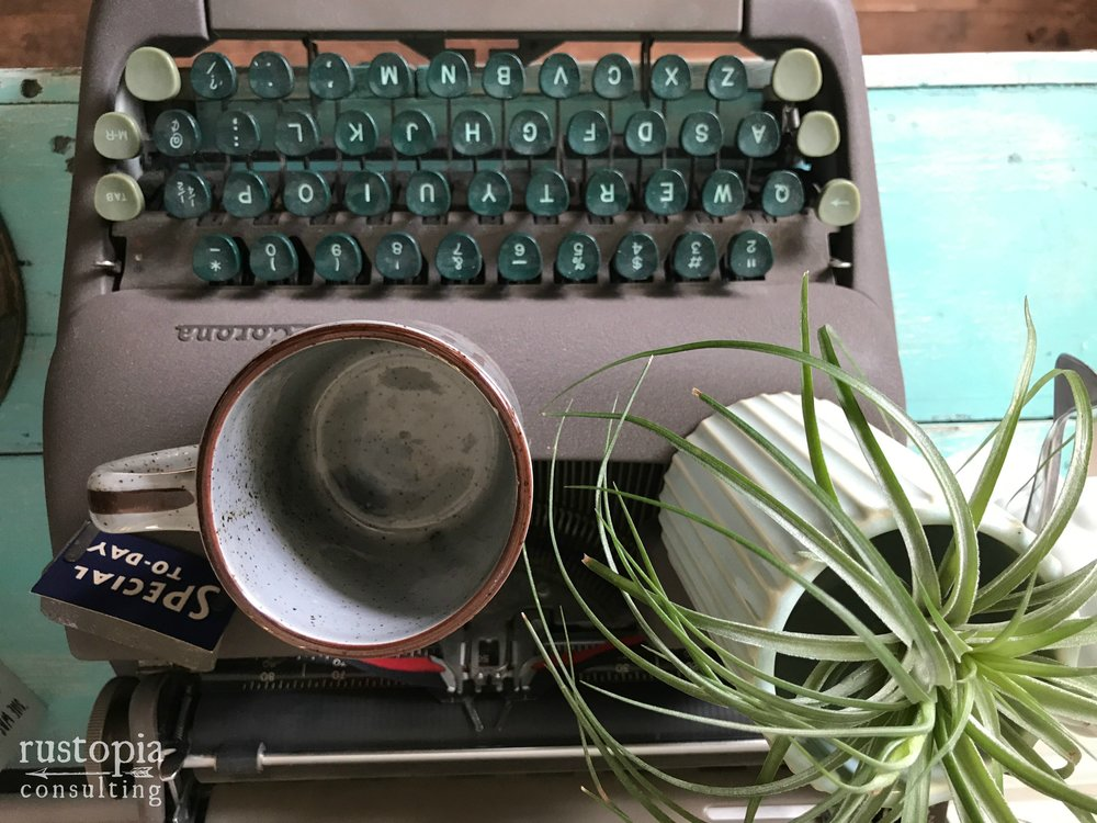 Empty coffee mug sitting on top of a vintage typewriter. || RustopiaConsulting.com