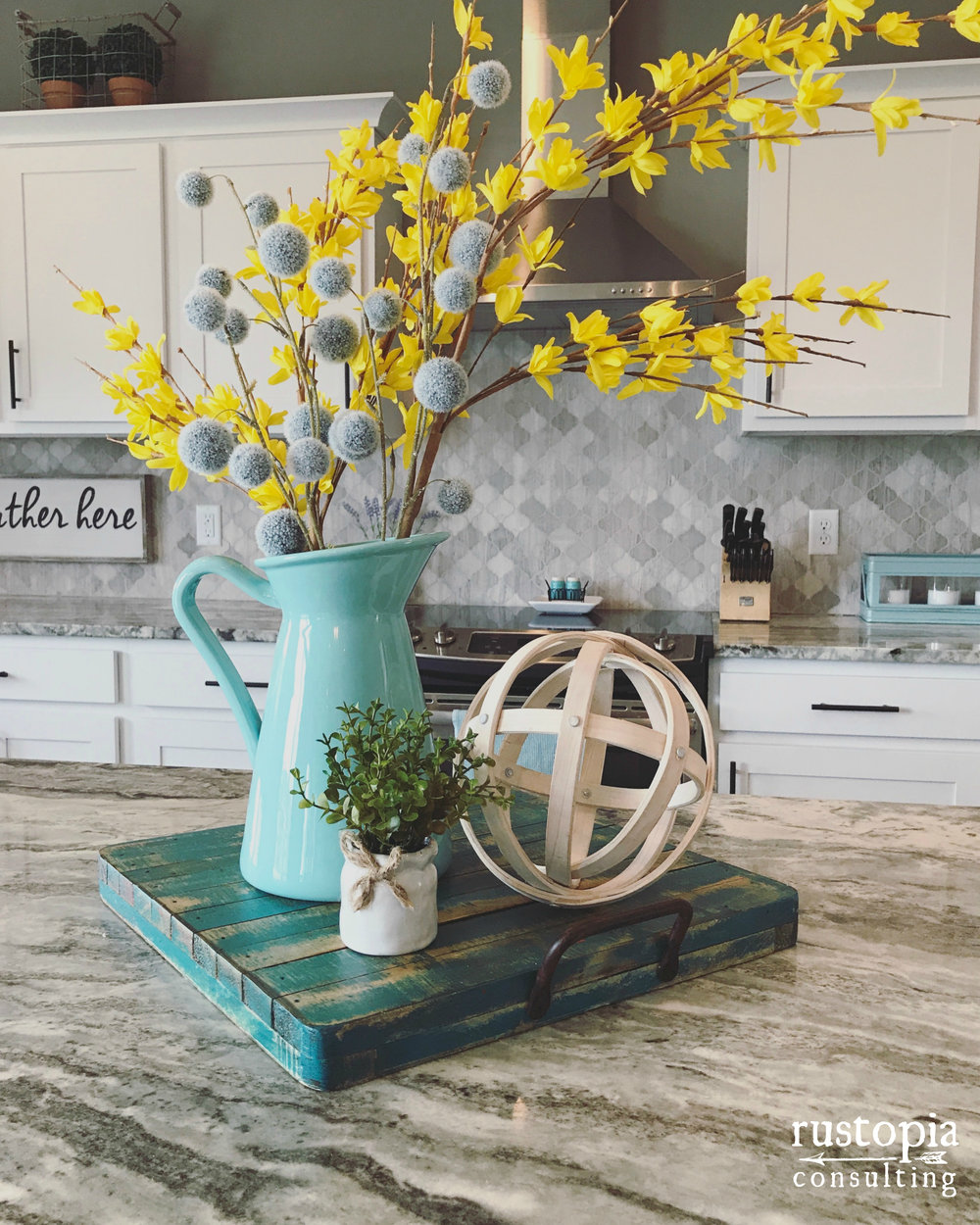 Kitchen vignette using a tray, pitcher, floral stems, and an orb. | RustopiaConsulting.com