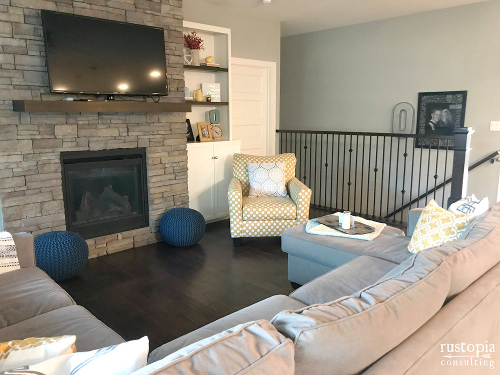Living room design with a sectional couch, a yellow accent chair, and blue floor poufs by RustopiaConsulting.com