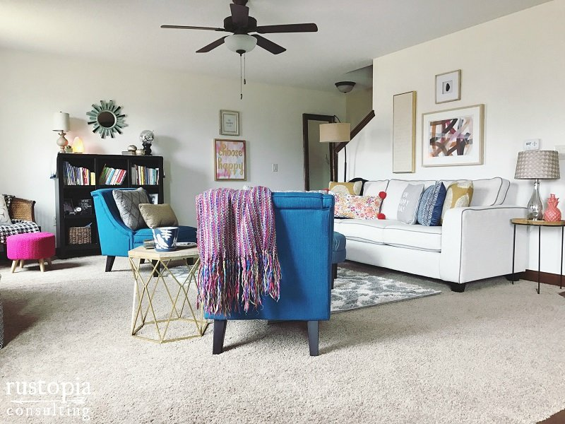 Living room design with blue accent chairs, and colorful throw pillows. | RustopiaConsulting.com